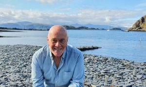 Donald Melville on a pebble beach with water behind him
