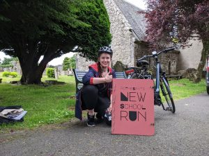 A cyclist pictured next to her bike holding a Rothesay's New School Run sign